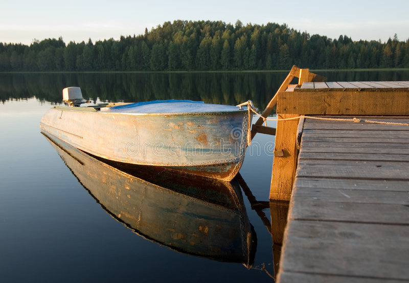 Boat reflecting in calm waters. Of forest lake stock photo