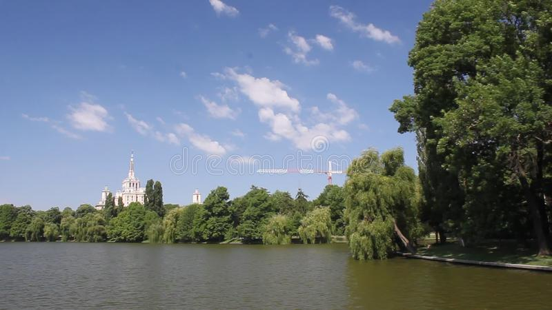 Boat ride on the lake. View on the bank with trees and Press House stock footage