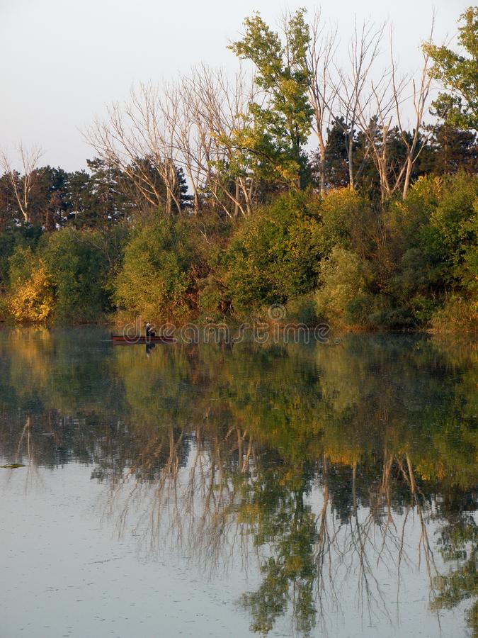 Boat and River in Autumn with Colorful Trees stock images