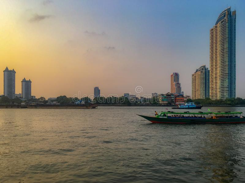 The boat in the river with  beautiful clear sunset sky and residential buildings stock photo