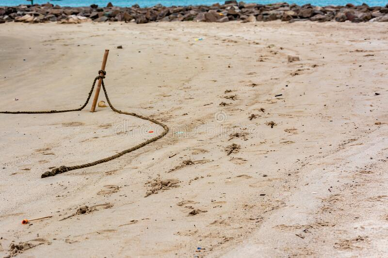 Boat rope and footprints on sand at beach royalty free stock image