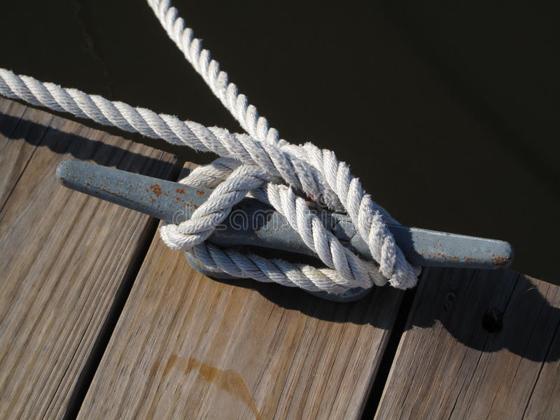 Boat Rope Tie Down. Boat tie down rope wrapped around dock cleat royalty free stock images