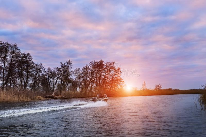 Boat rushing on a wild river in the early morning. stock image