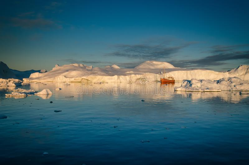 A boat sailing among the huge icebergs, Ilulissat Icefjord, Greenland royalty free stock photography