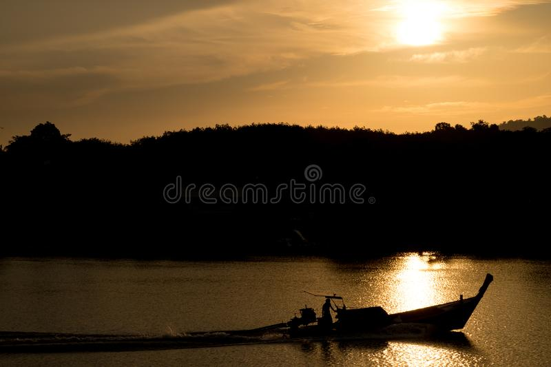 The boat is sailing in the river. The sunset is about to fall.Silhouette. stock images