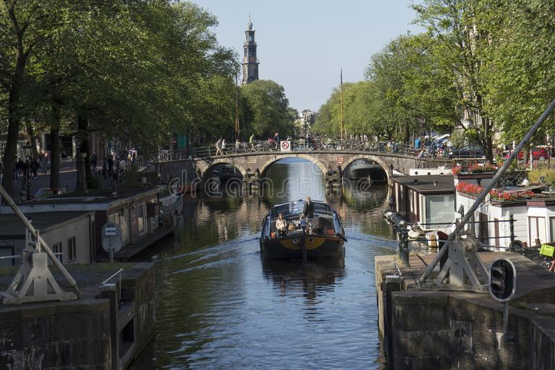 Boat sails by lock on the Prinsengracht with a view at the Westerkerk. Amsterdam, Holland - June 22, 2019:  Boat sails by lock on the Prinsengracht with a view stock photos
