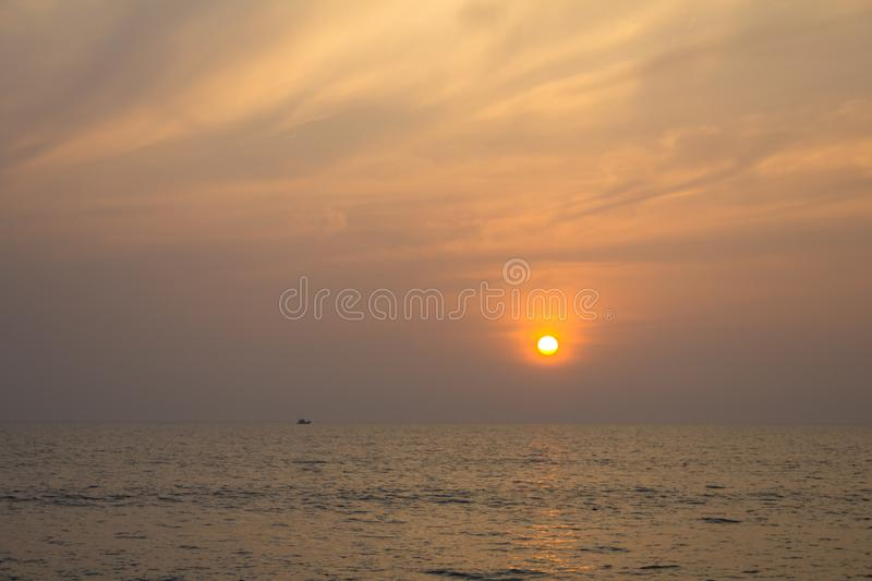 Boat in the sea on a background of purple sunset sky with bright yellow sun. A boat in the sea on a background of purple sunset sky with bright yellow sun royalty free stock images
