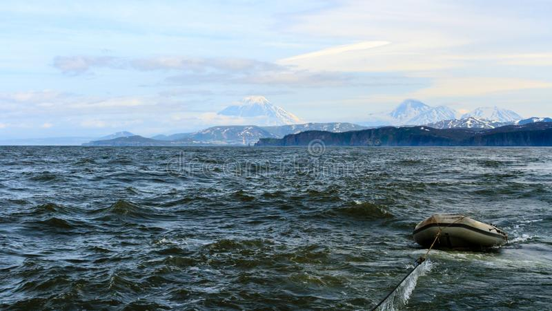 Boat in the sea. Beautiful view of the volcano Vilyuchinsky from ocean, Kamchatka Peninsula, Russia royalty free stock photo