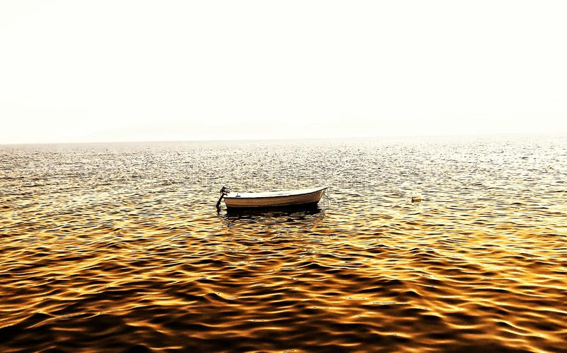 Boat on sea with golden reflection. Ocean royalty free stock images