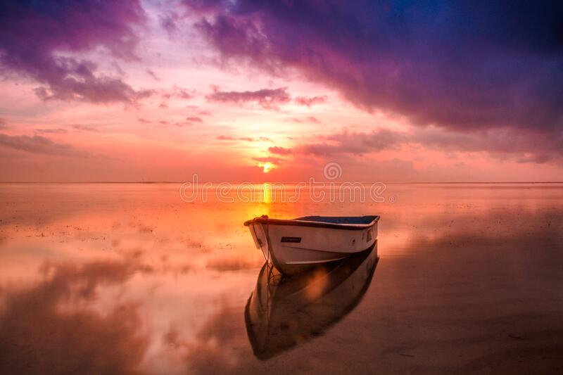 Boat on sea in magical dawn colors stock images