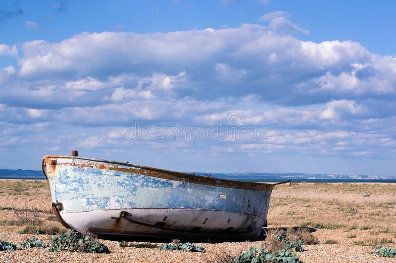 Boat on a shingle beach. Abandoned boat on a shingle beach on a sunny afternoon. The boat is rotting away. An impression of loneliness, nostalgia royalty free stock photo
