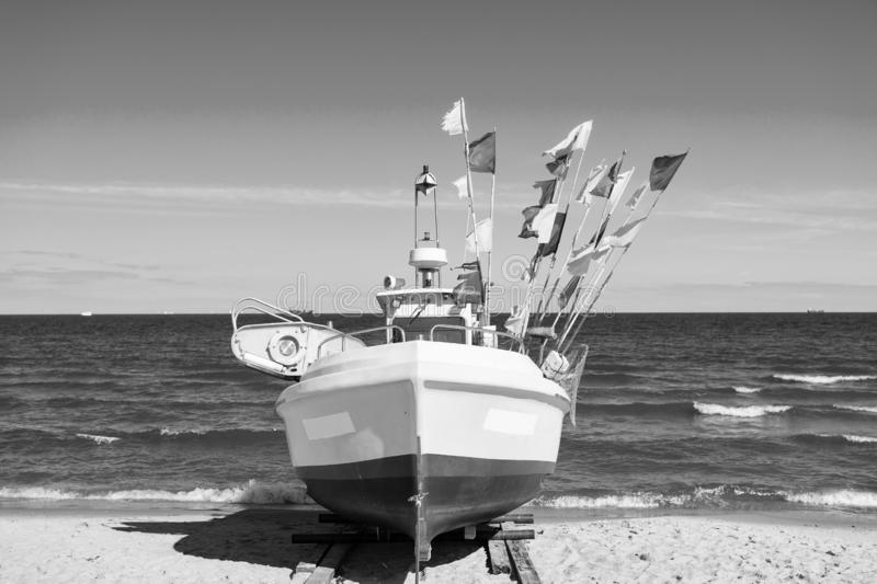 Boat or ship at moorage. Boat or ship modern marine vessel with colorful flags at moorage on beach on sunny day on blue sea and sky background royalty free stock photography