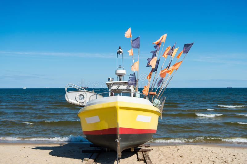 Boat or ship at moorage. Boat or ship modern marine vessel with colorful flags at moorage on beach on sunny day on blue sea and sky background stock photography