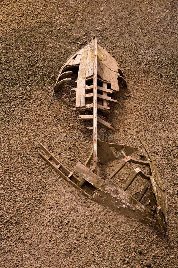 Boat ship skeleton half buried in sand stock image