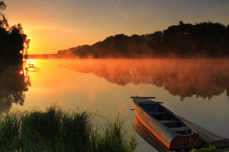 Boat on the shore of a misty lake stock images