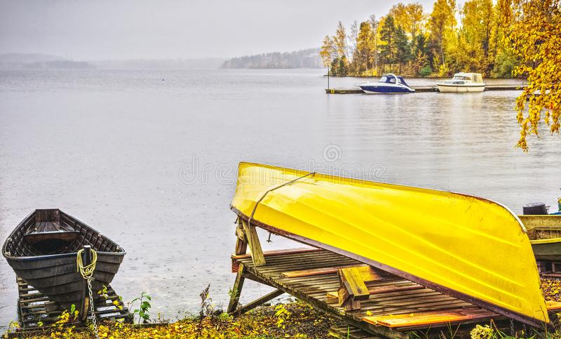 Boat on shores, Lake Pyhajarvi, Finland. Yellow canoe on shores with boats on waterfront of Lake Pyhajarvi, Tampere, Finland in fall stock photos
