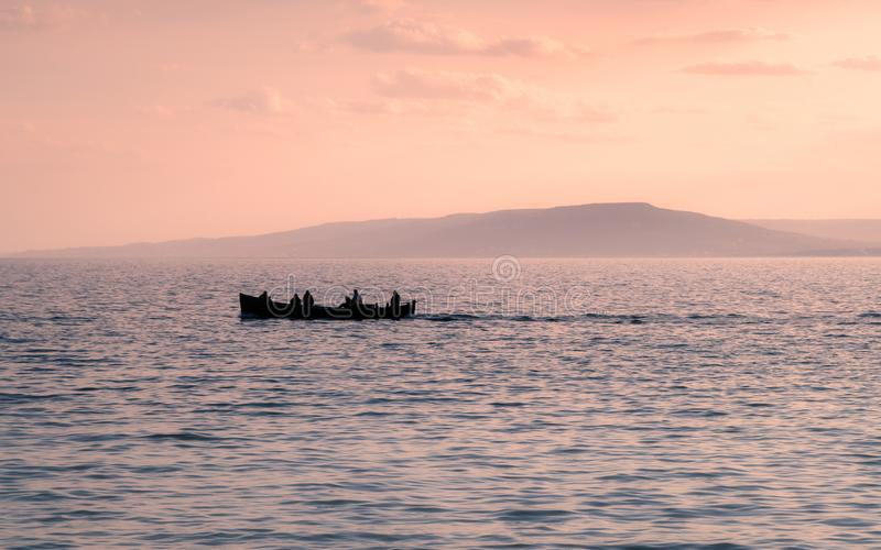 Boat silhouette with man on the water in sunset with mountain in. The background. Commercial fishing boat royalty free stock image