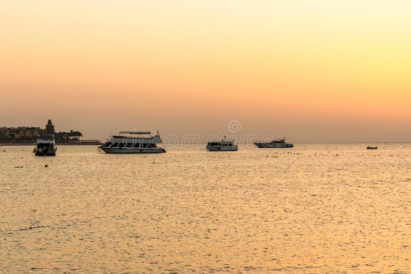 Boat silhouetts on the shores of the red sea at sunset in Makadi Bay Egypt golden colors stock photos
