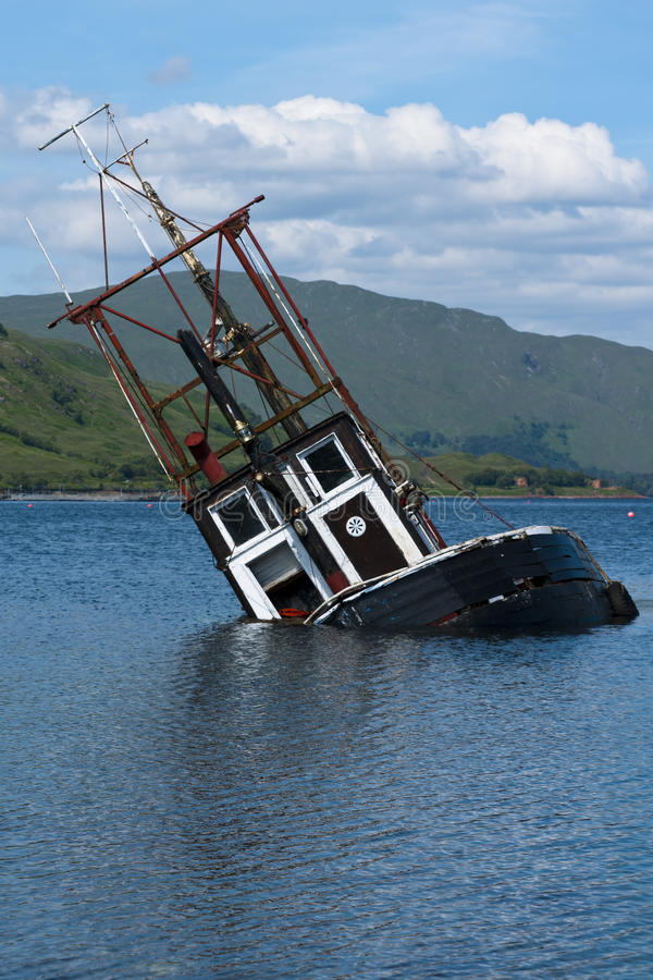 Boat, sinking. fishing vessel, Loch Linnie. A foundered and partially submerged fishing vessel or samon farm support vessel in Loch Linnie just north of the royalty free stock image