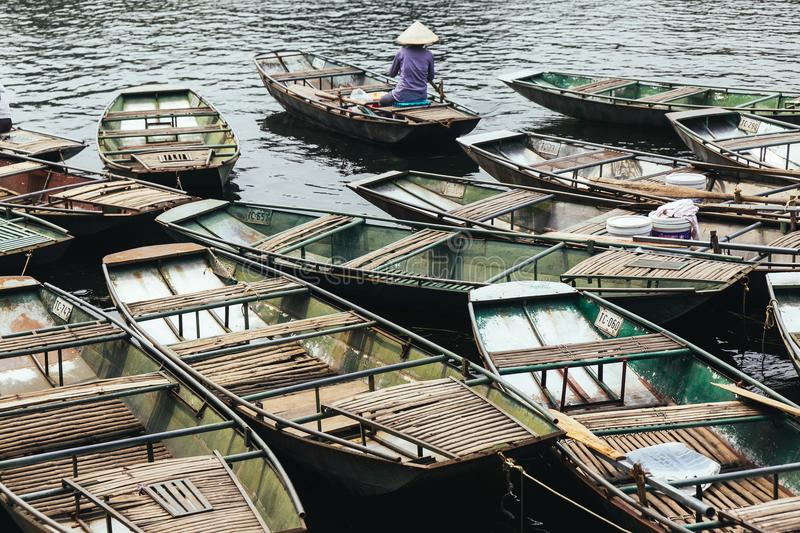 Boat stop on the river with many empty row boats, rowing men and women in summer at Trang An Grottoes in Ninh Binh, Vietnam royalty free stock photos