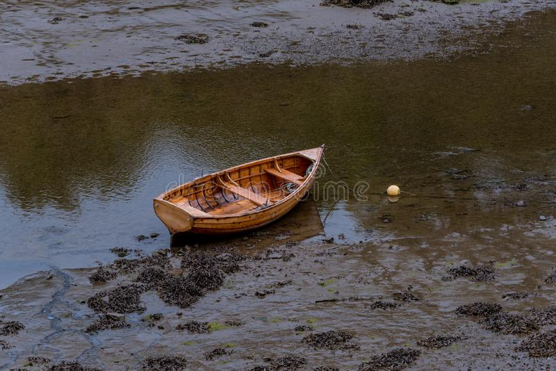 A Boat is Stuck in the Mud. A Rowboat is anchored the muddy water because of a drought stock photos
