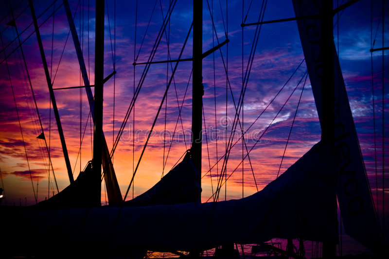 Boat Sunset. Three sailboats during colourful sunset with red sky and blue clouds - Barcolana event in Trieste - Italy 2007 stock image