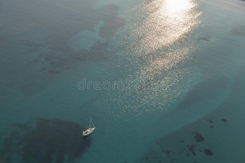 Boat at sunset on emerald waters. Wide space, opens, relax, leisure, loneliness stock photography
