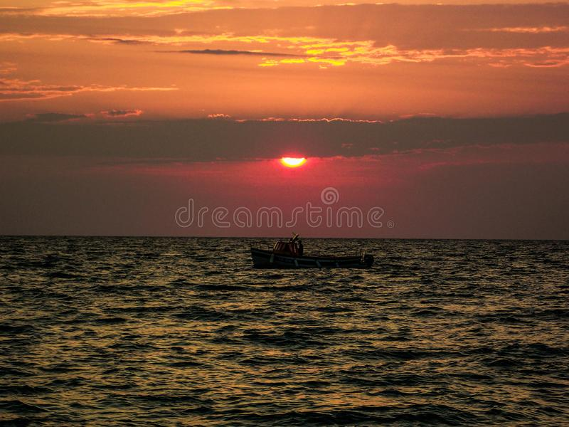 The boat in the sunset. The man in the boat goes lonely through sea in the sunset. Maybe, he`s coming home stock image