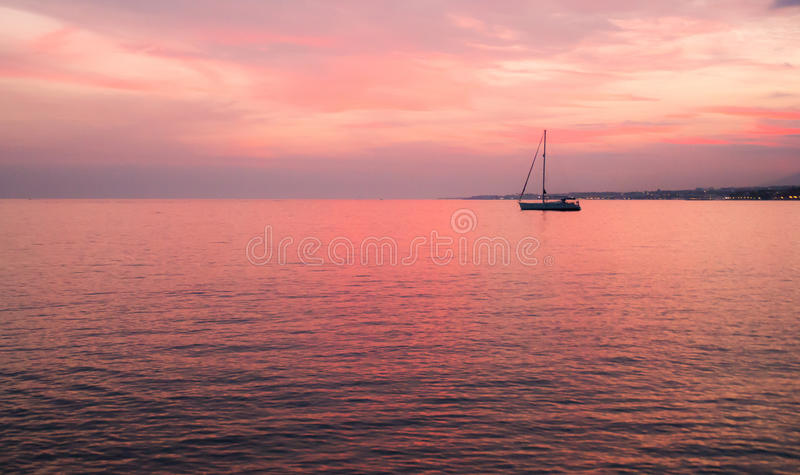 Boat at the sunset. A peacefull boat in the sea at sunset stock images