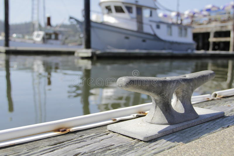 Boat Tie off with Yacht in Background docked. Close up of a boat tie off on a dock with a yacht in the background stock photography