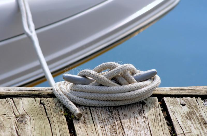 Boat Tied To Dock. Boat tied securely alongside boating dock royalty free stock image