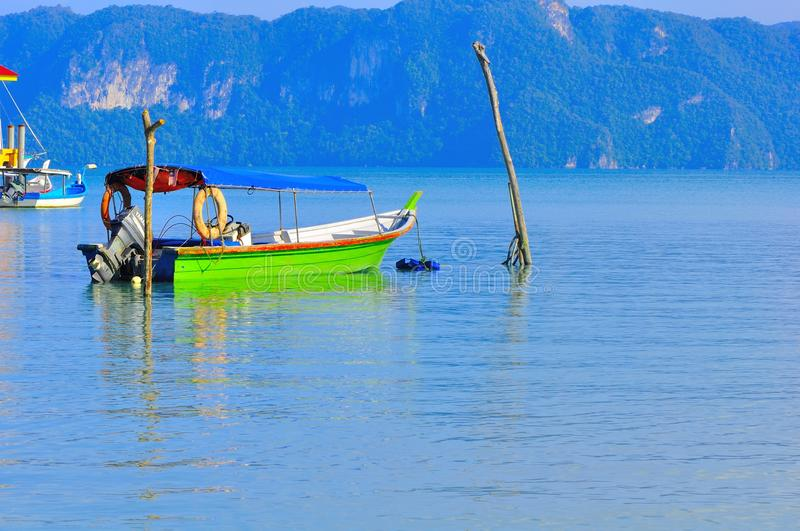 Boat tied to two wooden poles in Langkawi Island stock images