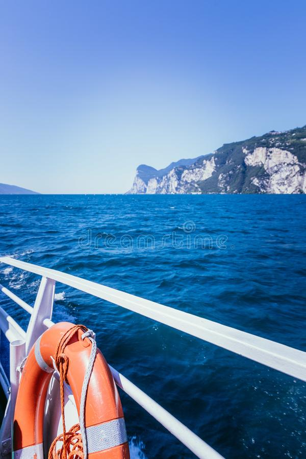 Boat tour: Boat railing, view over azure blue water and mountain range. Lago di Garda, Italy stock photo