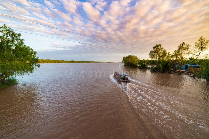Boat tour in the Mekong River Delta region, Ben Tre, South Vietnam. Wooden boat on cruise in the water channel through coconut royalty free stock image