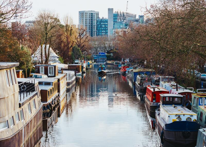 Boat traveling between parked houseboats through a canal in Little Venice district, London arkivfoto