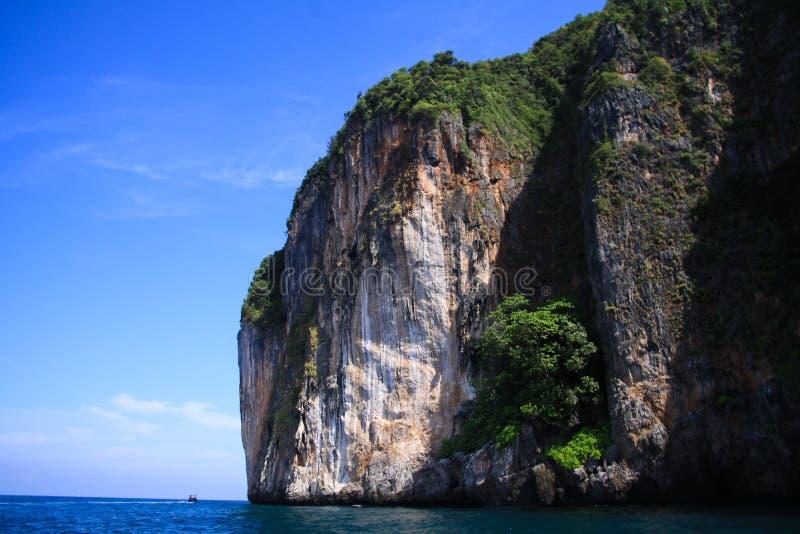 Boat trip along the coast line of tropical island Ko Phi Phi along impressive rock formations under blue sky stock photo