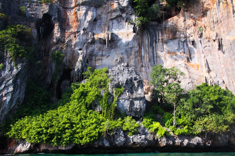 Boat trip around impressive steep rough cliffs of tropical island Ko Phi Phi, Thailand royalty free stock images