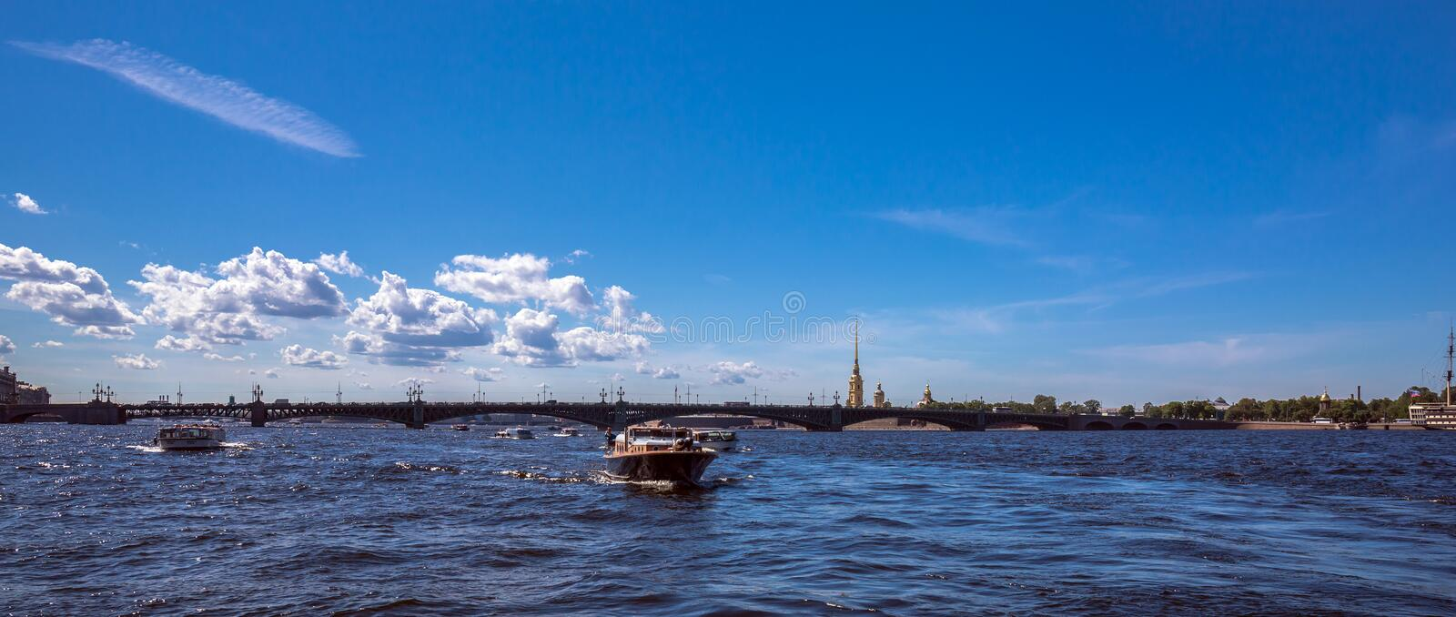 Boat trip by Neva river of Saint Petersburg under blue summer sky with bright clouds royalty free stock photography