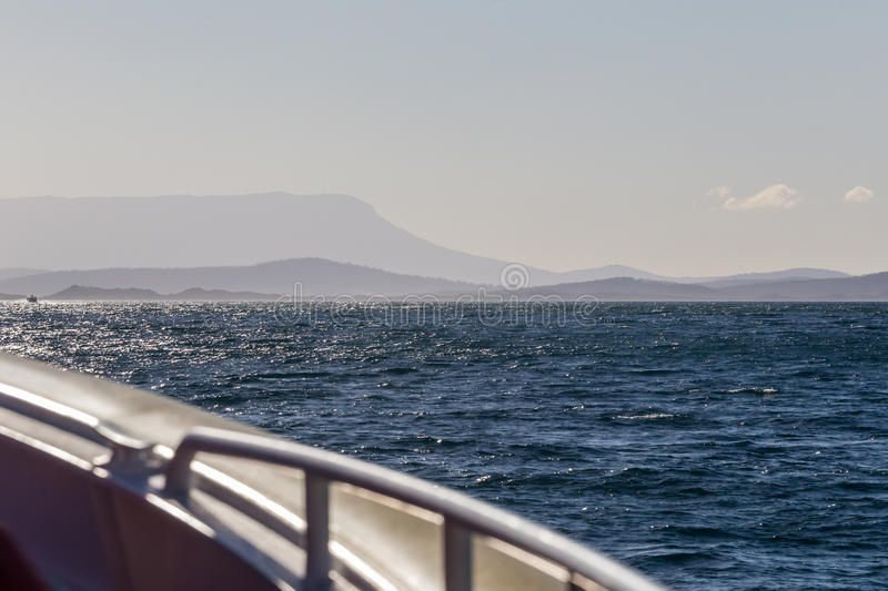Boat trip on the Tasman Sea. During a boat trip on the Tasman Sea, remote coastlines of the mainland and islands are visible as shades of blue royalty free stock photography