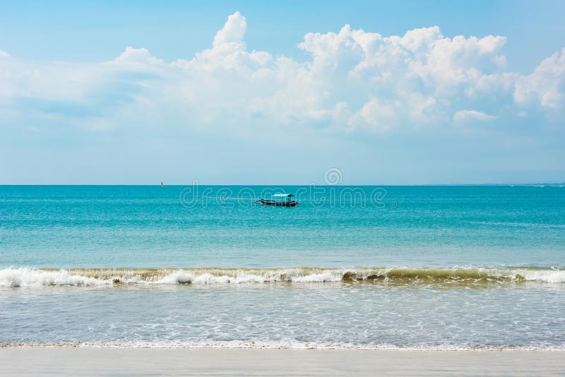 Boat on turquoise water, Bali. Wooden small boat with turquoise sunshade. White clouds, blue sky over ocean, perfect day, holidays stock photo