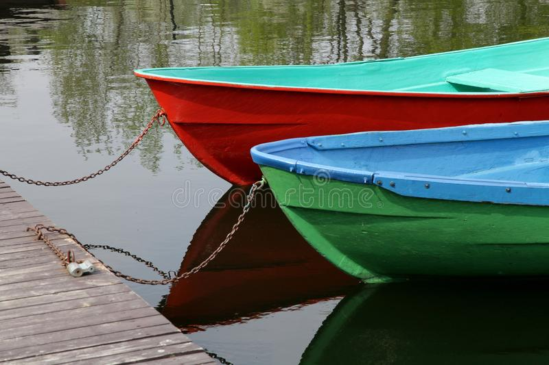 Boat, vacation, tourism, green and red boats parked ashore. Green and red boats parked ashore on a lake, boat, vacation, tourism royalty free stock image