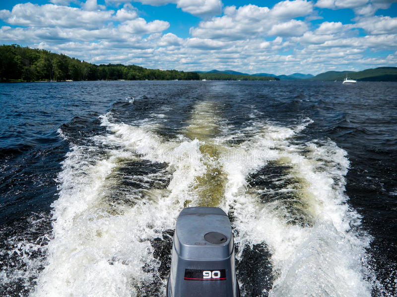 Boat wake with outboard engine. On a lake with boats in the background royalty free stock images