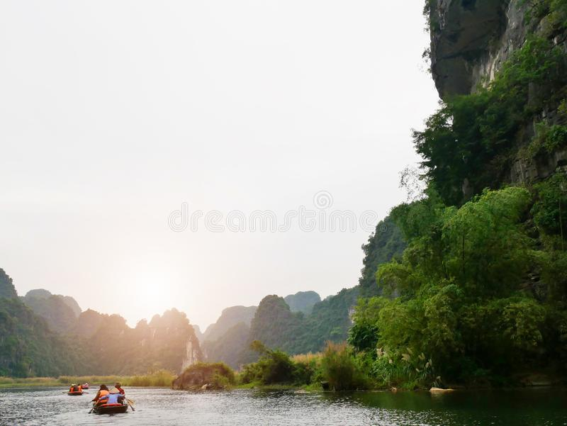 The boat that was paddling along the waterway with high mountains. In Halongbok, Vietnam royalty free stock photo