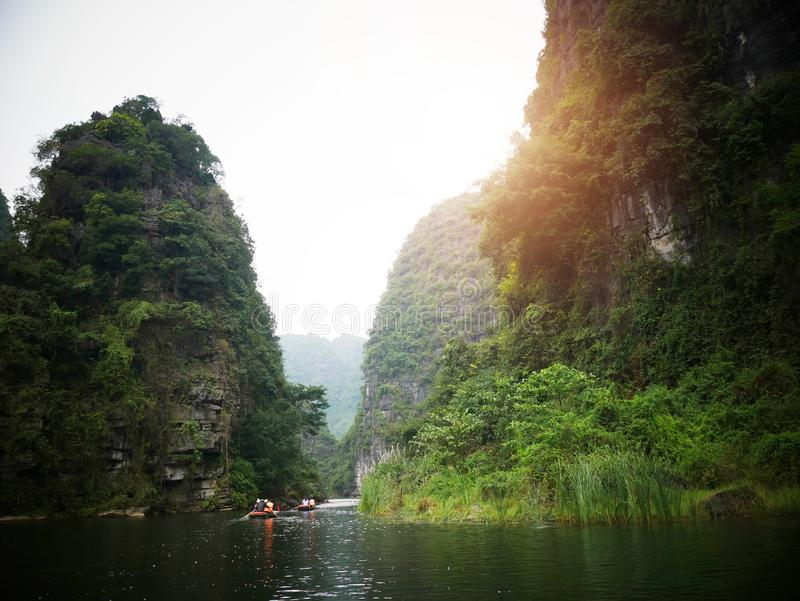 The boat that was paddling along the waterway with high mountains. In Halongbok, Vietnam royalty free stock images