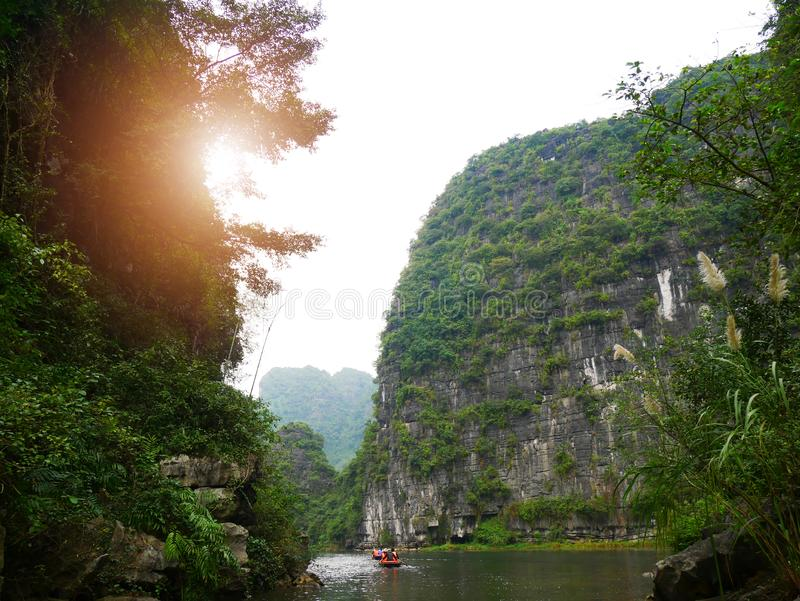 The boat that was paddling along the waterway with high mountains. In Halongbok, Vietnam stock photography