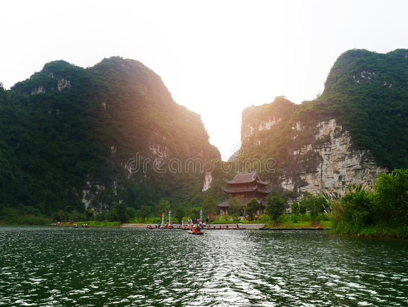 The boat that was paddling along the waterway with high mountains. In Halongbok, Vietnam stock image