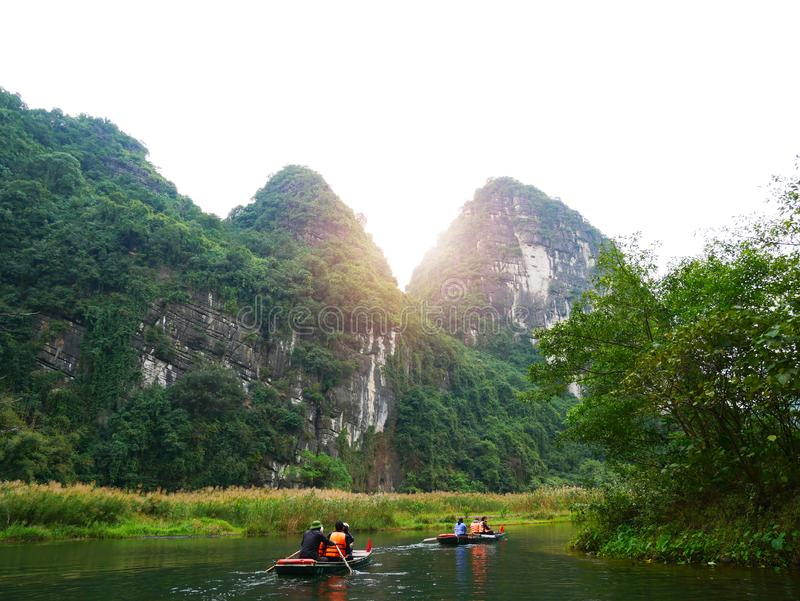 The boat that was paddling along the waterway with high mountains. In Halongbok, Vietnam stock photo
