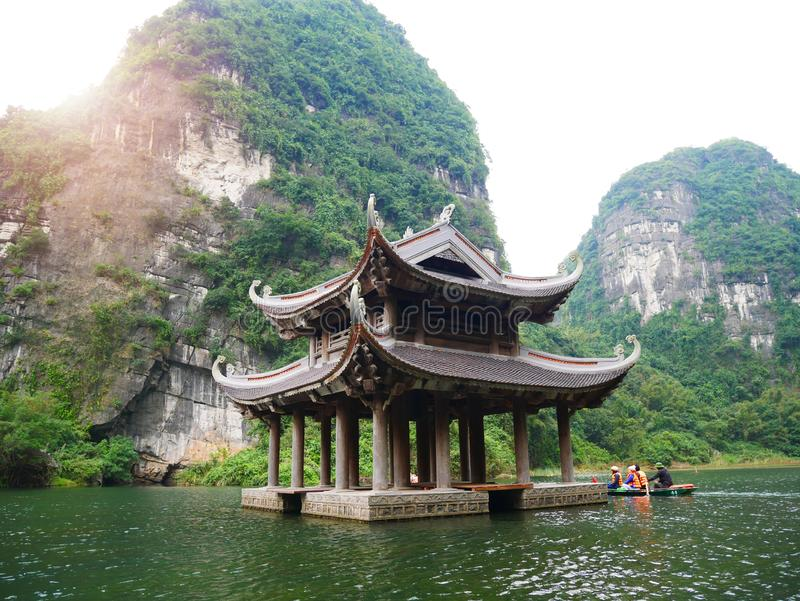 The boat that was paddling along the waterway with high mountains. In Halongbok, Vietnam royalty free stock image