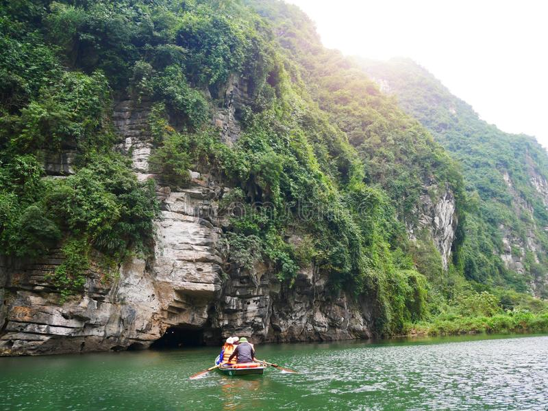 The boat that was paddling along the waterway with high mountains. In Halongbok, Vietnam stock photos