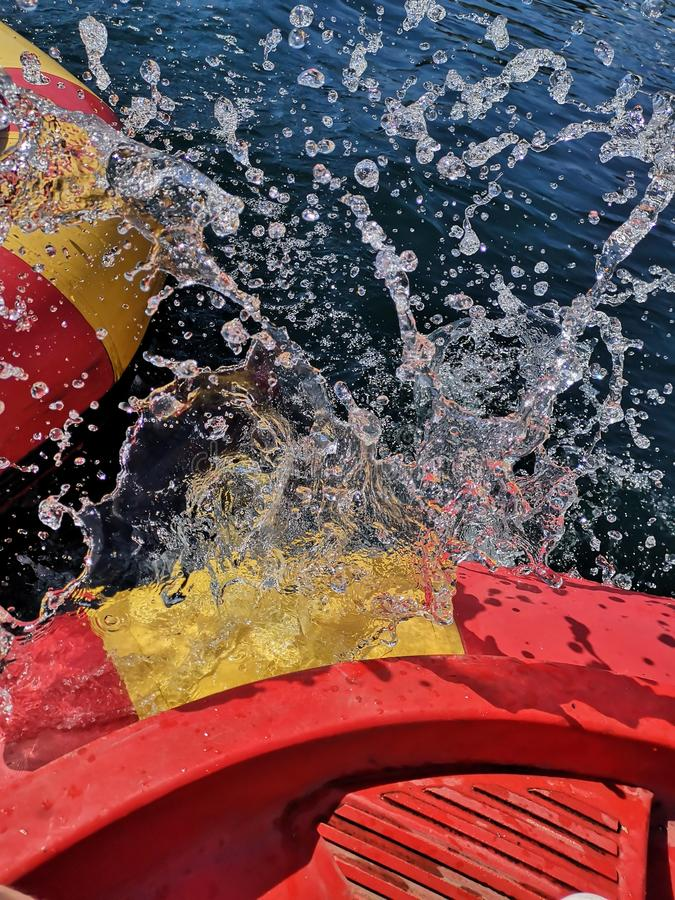 Boat Water Splash. Water Splashing with boats colliding. Bumper boats on holiday. Water droplets splashing and spraying upwards. Red and yellow boats royalty free stock images